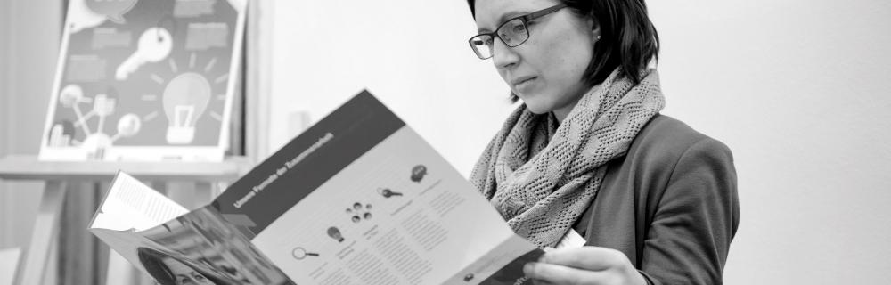 Teilnehmerin liest im Flyer der Transferagenturen