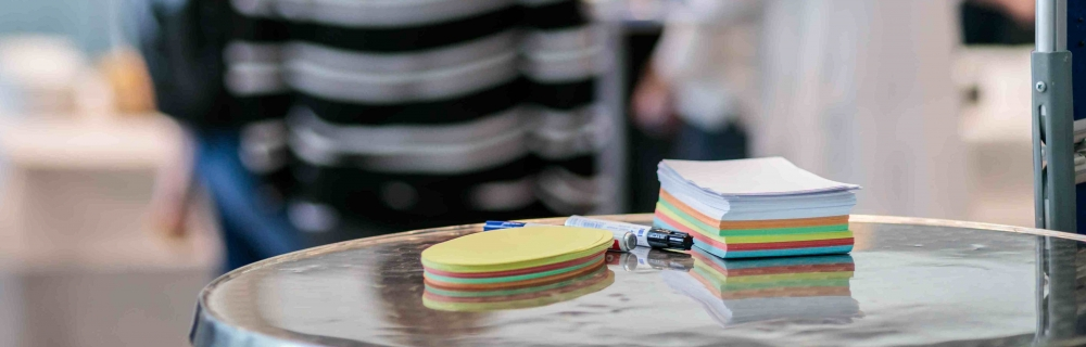 Stapel Moderationskarten und Stifte liegen auf dem Tisch