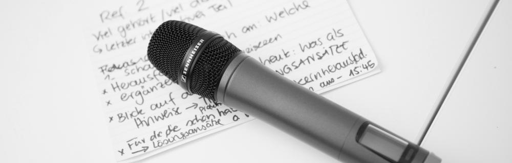 Mikrofon liegt auf einer beschriebener Karteikarte
