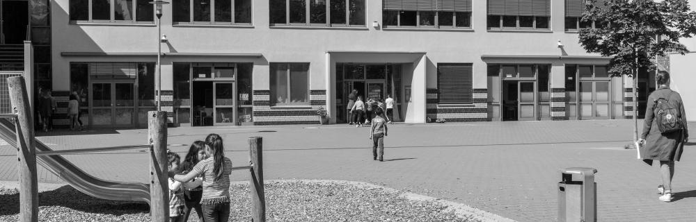 Schulgebäude mit Spielplatz und Kindern davor