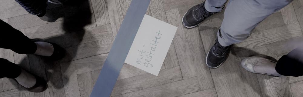 """Vogelperspektive auf einen Kreis aus Füßen um einen Zettel auf dem steht: """"mitgestaltet"""""""