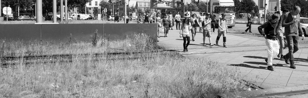 Menschen überqueren Bahnübergang