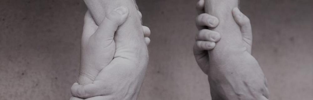 Zwei Paar Hände halten sich aneinander