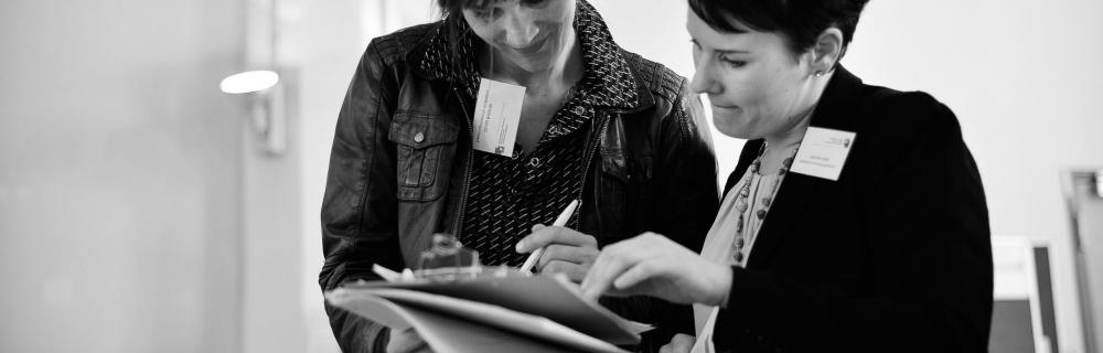 zwei Frauen schauen in eine Publikation