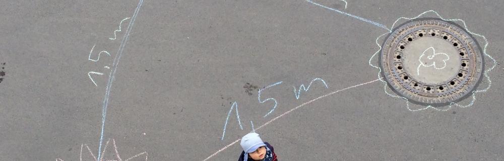 Kind aus Vogelperspektive auf Asphalt stehend, wo mit Kreide der Abstand in Corona-Zeiten aufgemalt ist