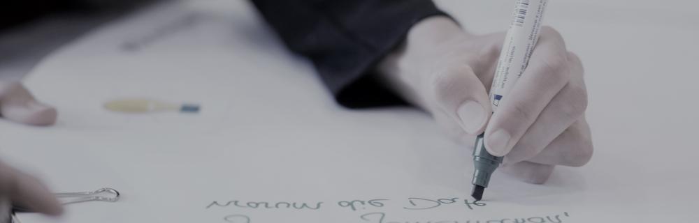 Hand schreibt auf Tisch
