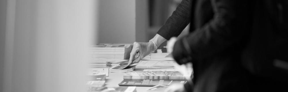 Menschen greifen nach Publikationen auf einem Tisch
