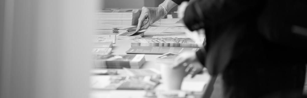 Teilnehmer:innen greifen nach Publikationen auf einem Tisch