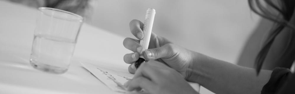 Hand schreibt auf eine Karteikarte