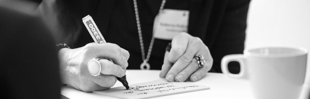 Hand schreibt mit Edding auf Papier