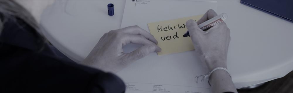 """Frau schreibt """"Mehrwert"""" auf Moderationskarte"""