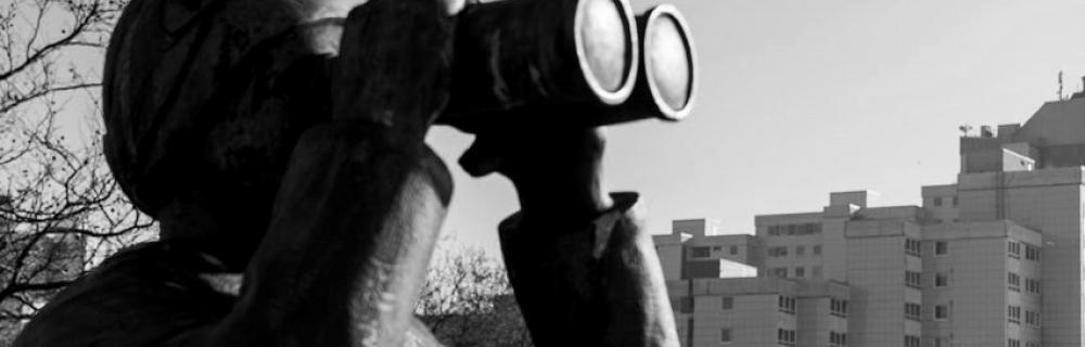 Statue mit Fernglas blickt in die Ferne