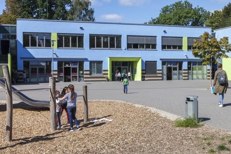 Frontansicht einer Schule in Dortmund mit Spielplatz davor