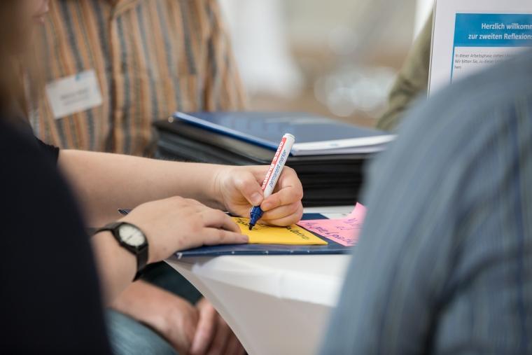 Hand schreibt auf Moderationskarten